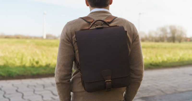 Man wearing the the vegetable-tanned brown leather backpack.