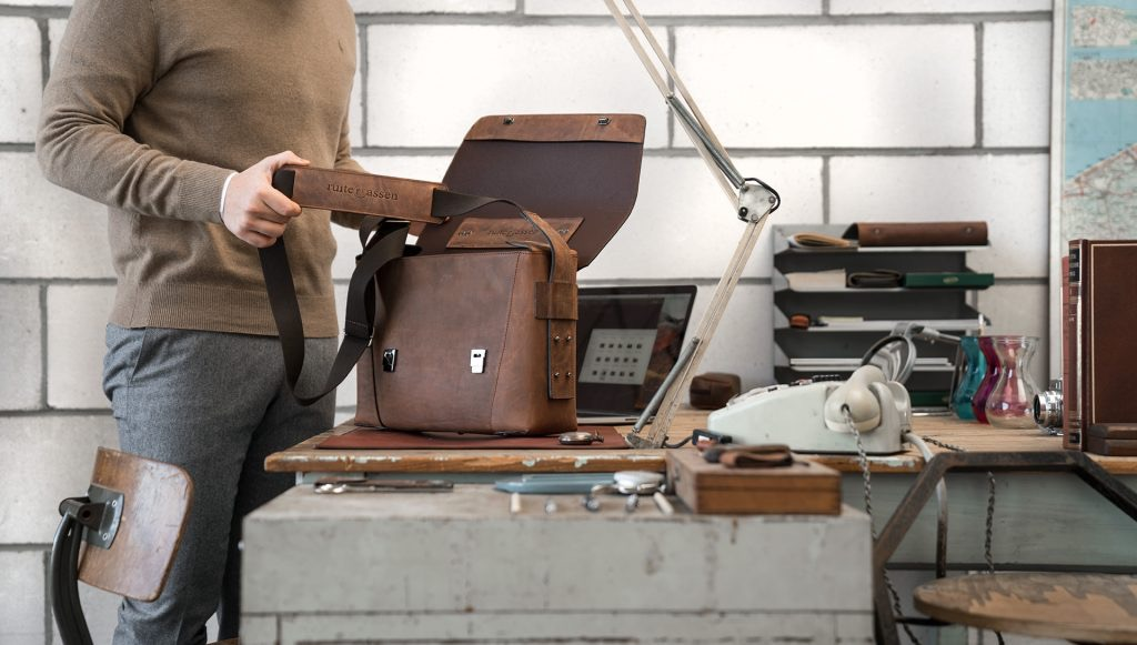 Man using the vegetable-tanned brown leather briefcase bag with laptop pocket.