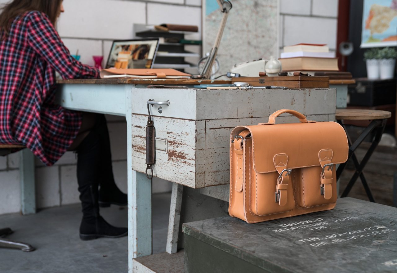 Woman in her office with her Ruitertassen tan leather satchel briefcase.