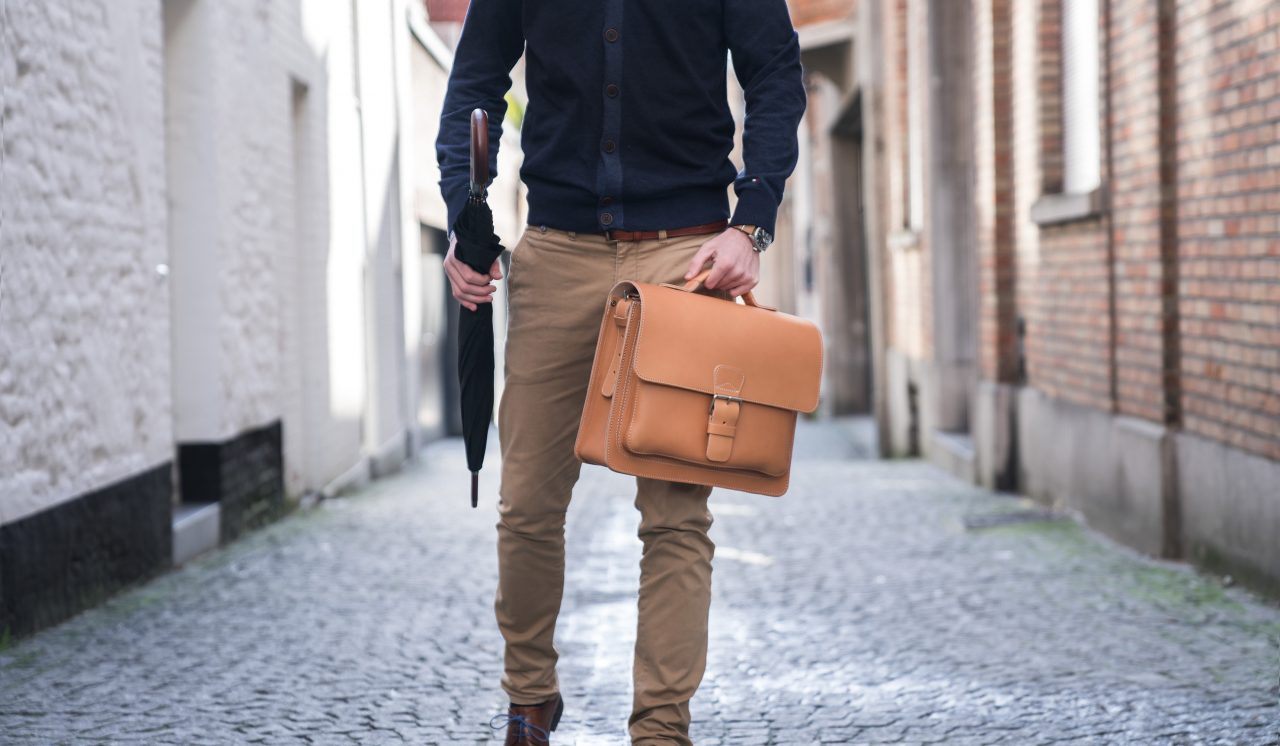 Elegant man carrying his tan leather briefcase by the handle.