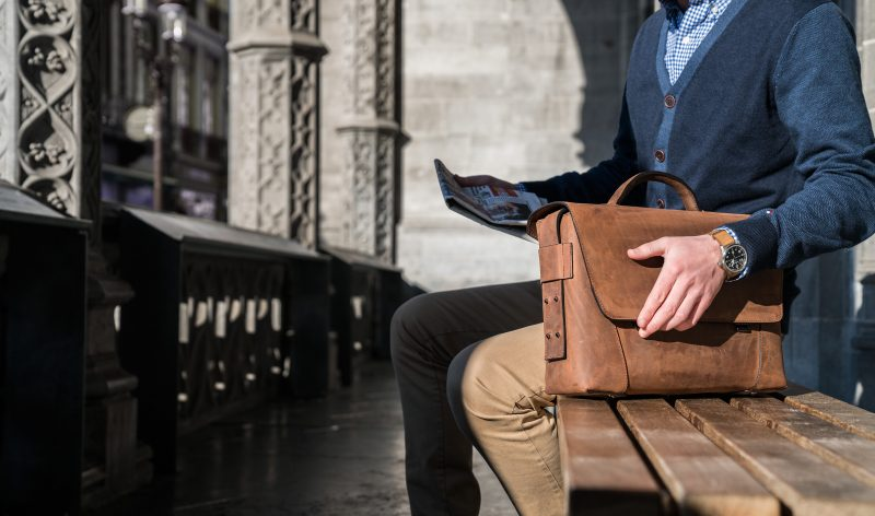 Man sitting with the vegetable-tanned brown leather briefcase bag with laptop pocket.