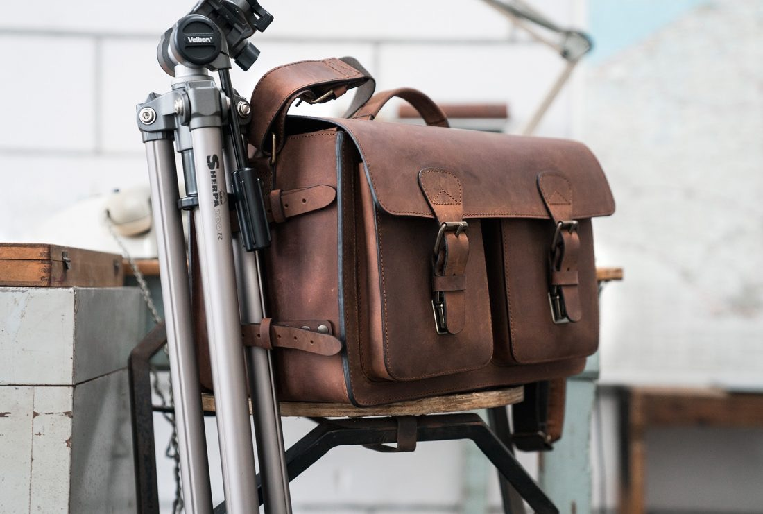 Large brown leather camera bag with tripod holder.