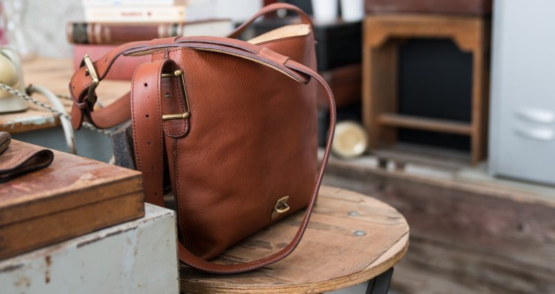 Luxury soft vegetable-tanned brown leather crossbody bag for men on a stool.