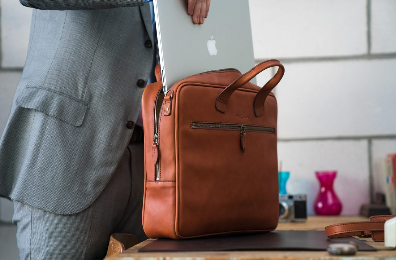 Man fitting his laptop in the luxury brown vegetable-tanned leather briefcase.