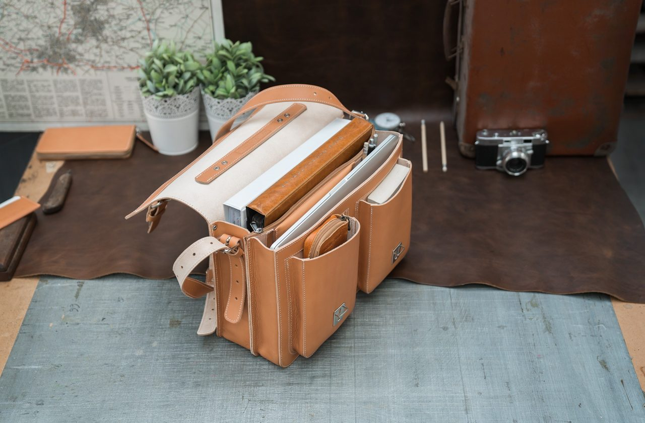 Open tan leather satchel for professors with files, book and macbook laptop.