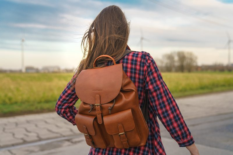 Woman wearing the elegant brown soft leather backpack.