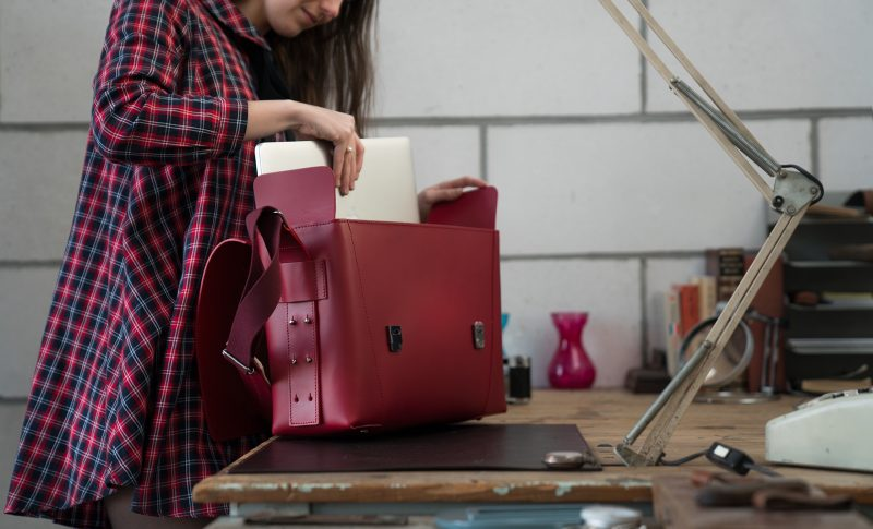 Woman fitting her macbook in the large red vegetable-tanned leather briefcase bag with laptop pocket.