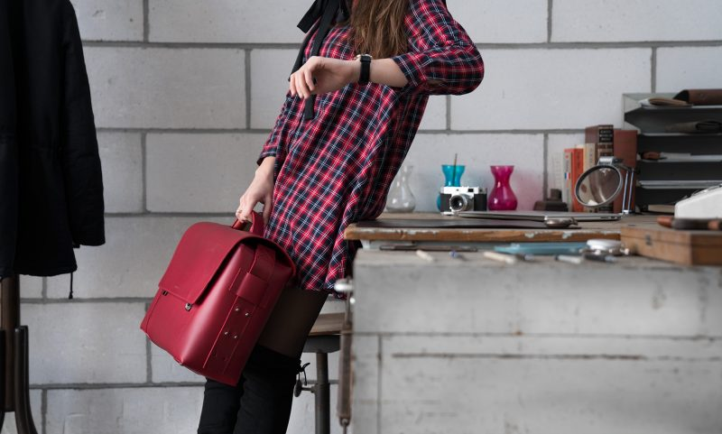 Woman holding the large red vegetable-tanned leather briefcase bag.