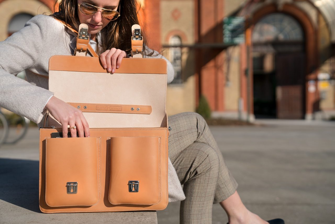 Women opening her tan leather satchel briefcase made by Ruitertassen.