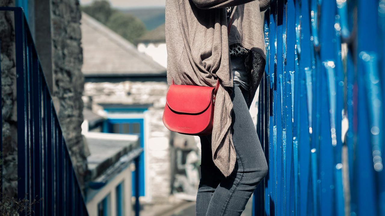 Woman wearing a small red leather shoulder bag.
