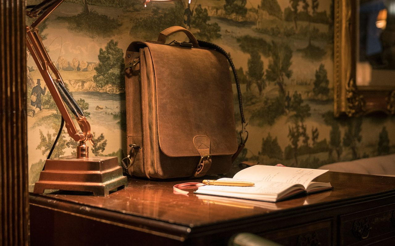 Beautiful leather bag on writer's desk.