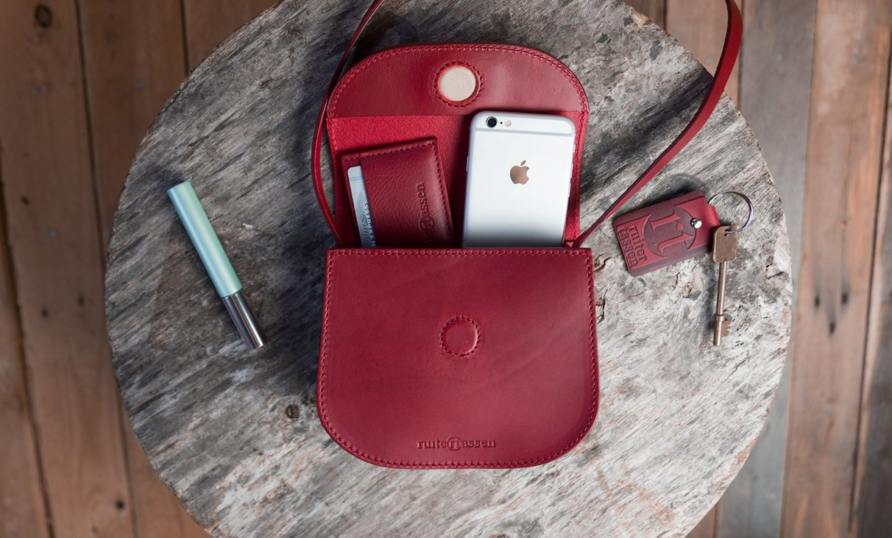 Small red leather shoulder bag open with accessories.