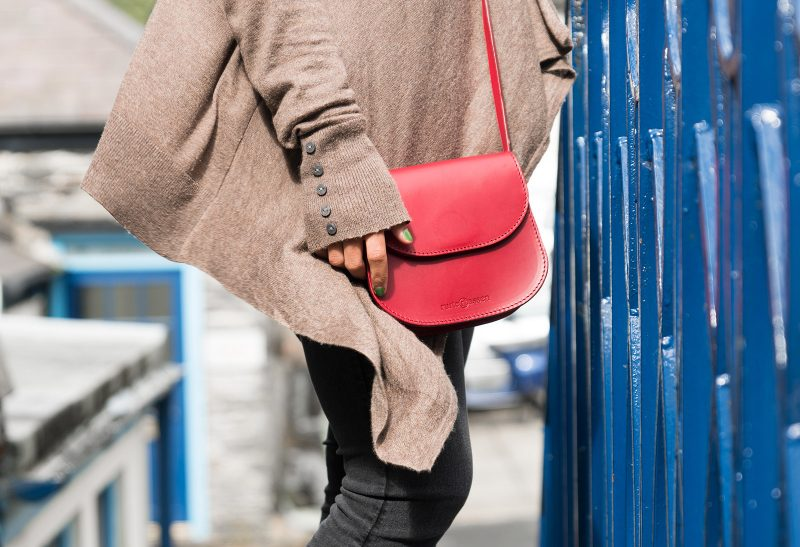 Woman with red leather shoulder bag.