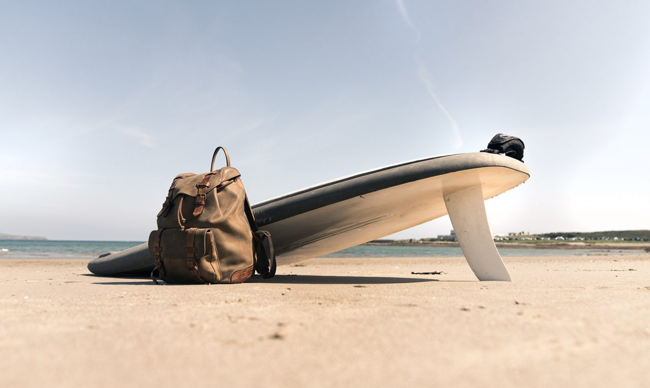 Beautiful leather backpack on the beach.