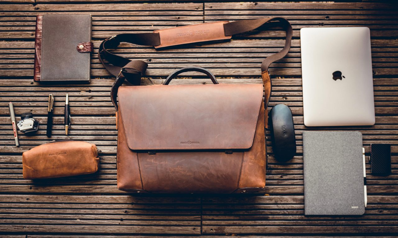 Stylish brown leather briefcase with work accessories.