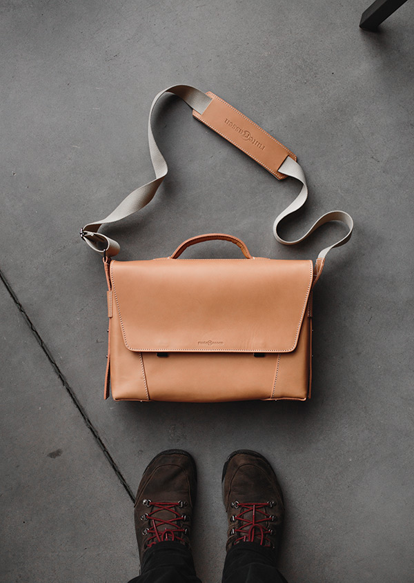 Tan leather briefcase on concrete floor.