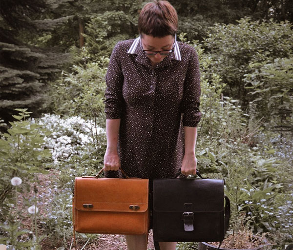 Woman wearing vintage vegetable-tanned leather satchels.