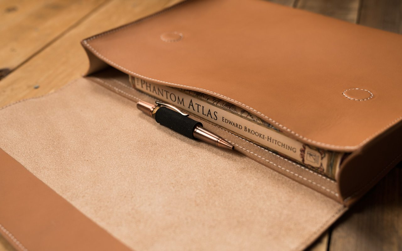 Book and pen in a leather document folder.