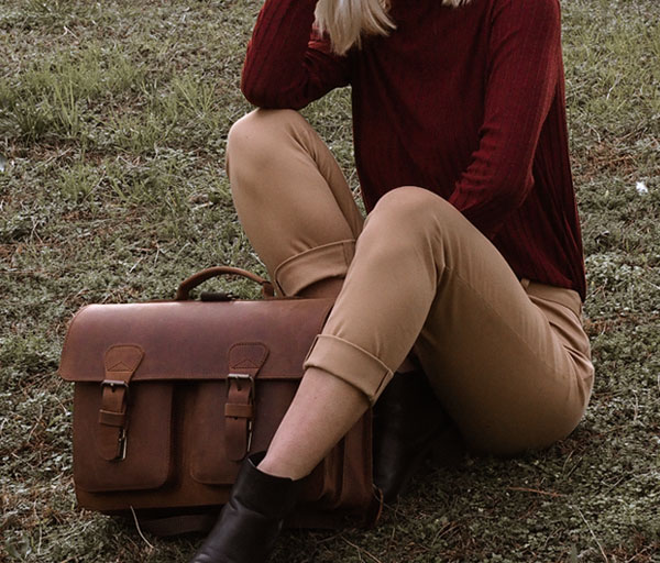 Woman sitting with her vegetable-tanned leather satchel.