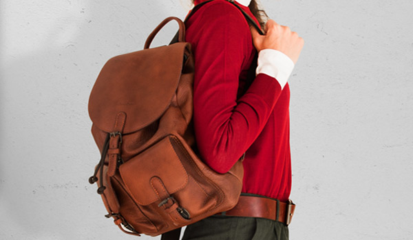 Women wearing a large supple leather backpack.
