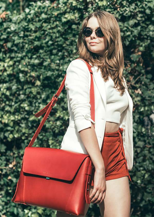 Business Woman wearing a red leather messenger bag.