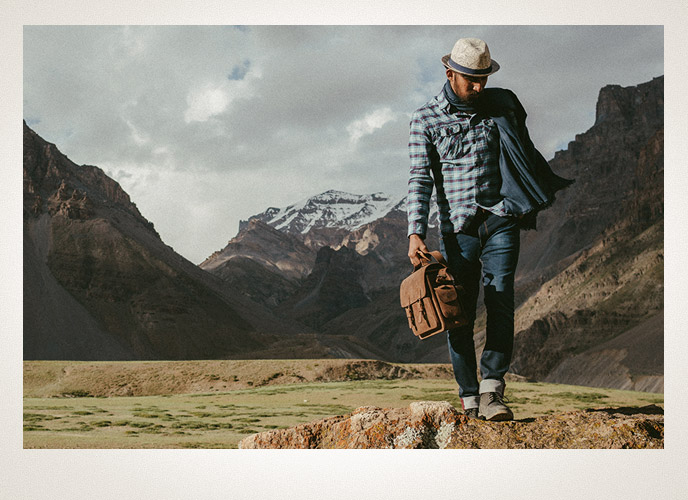Man carrying a brown leather camera bag in beautiful landscape.