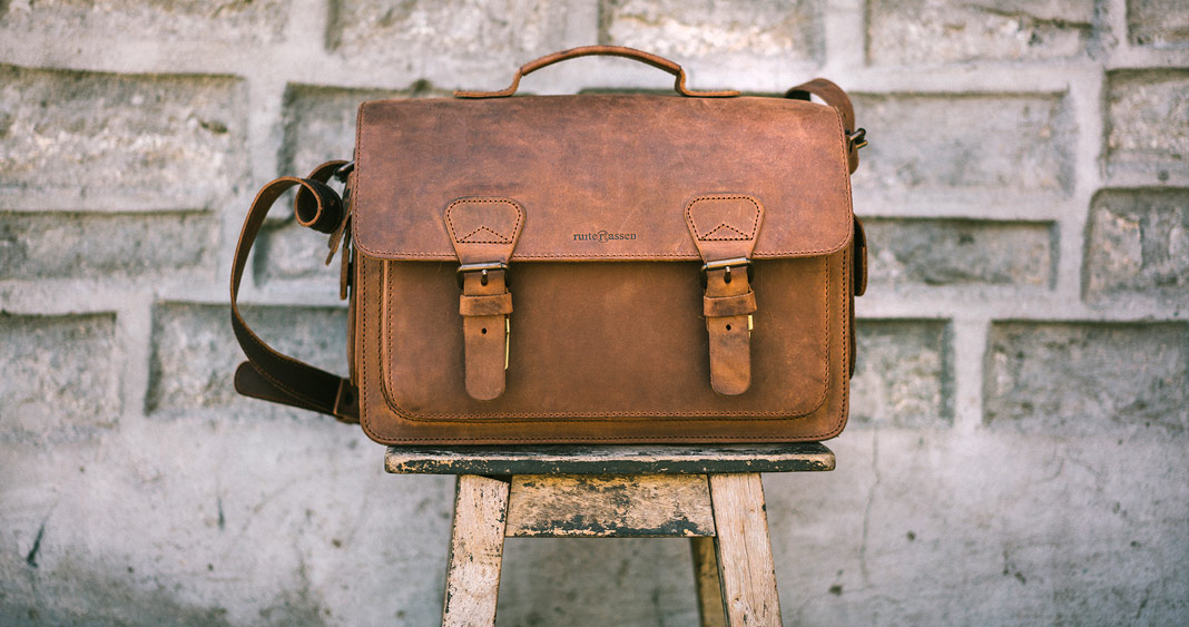 Beautiful brown leather camera bag on a wooden stool.