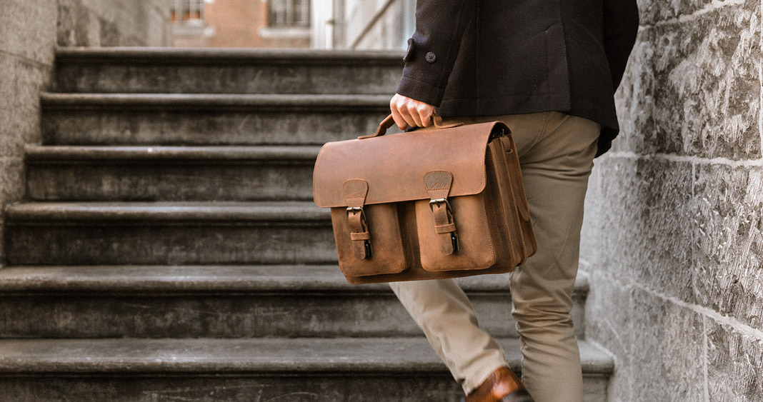 Man wearing a brown leather satchel on stairs.