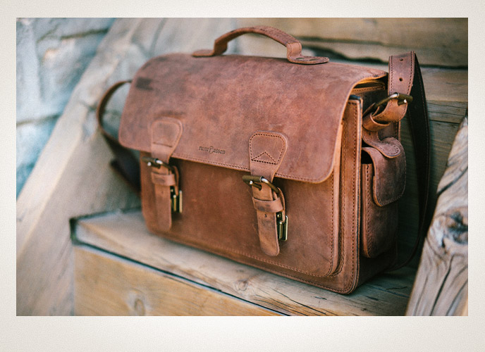 Vintage leather camera bag on a bench.