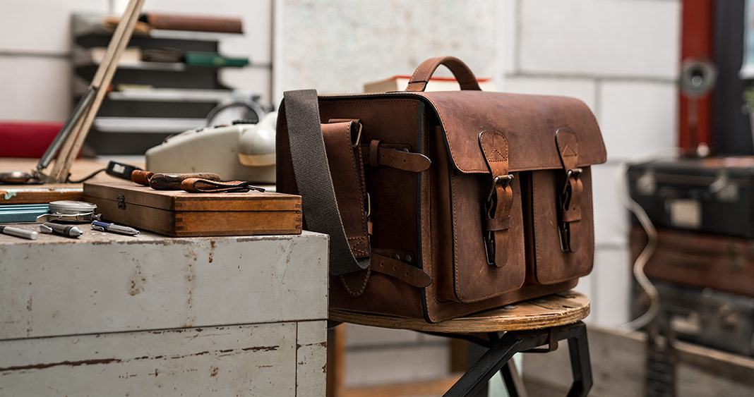 Large brown leather camera bag on a stool in an office.