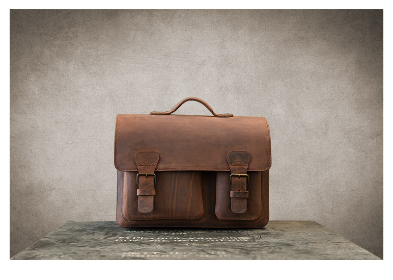 Large brown leather satchel on vintage military box.