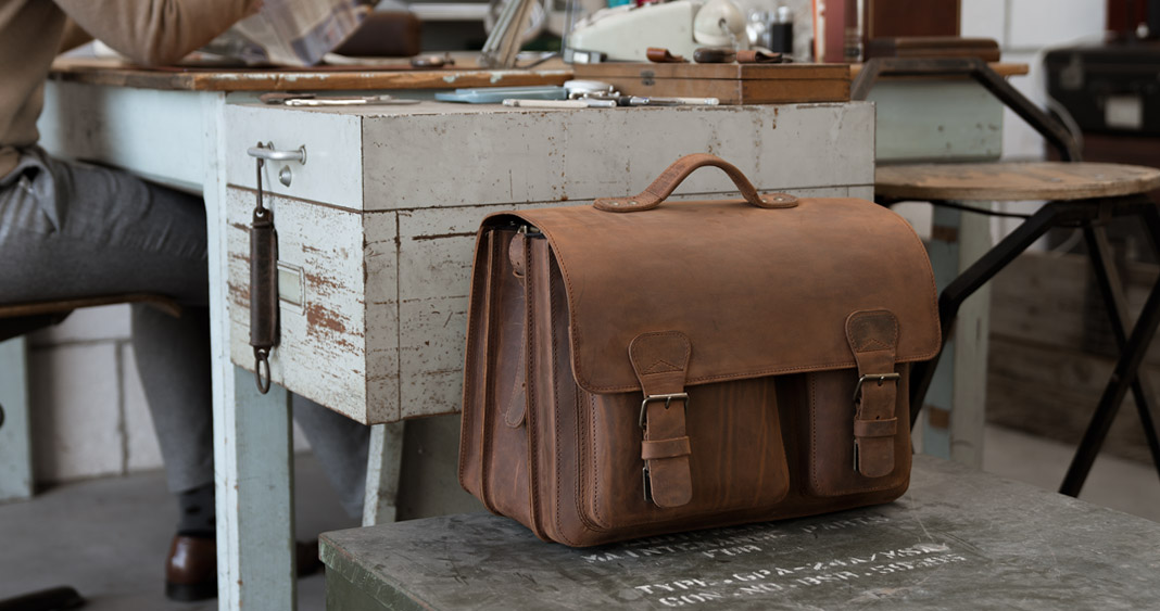Large brown leather satchel briefcase in an office.