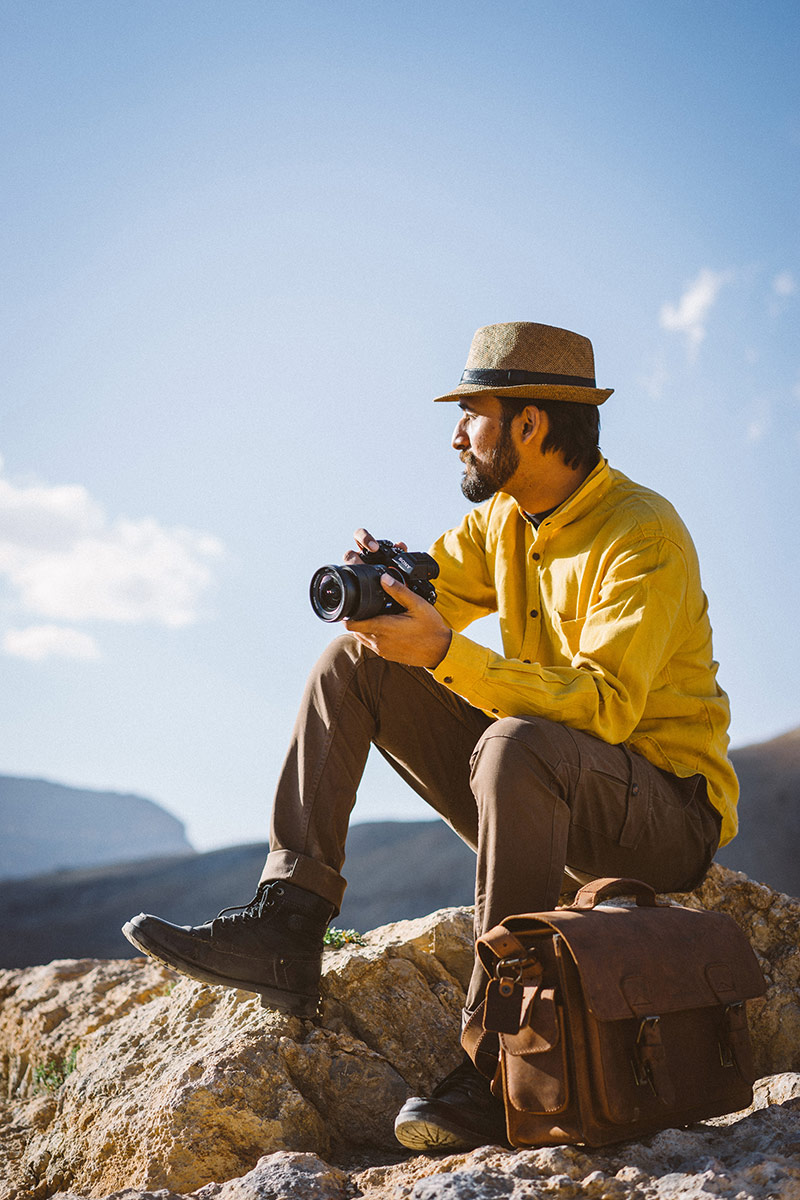 Photographer sitting in the mountains with a camera.