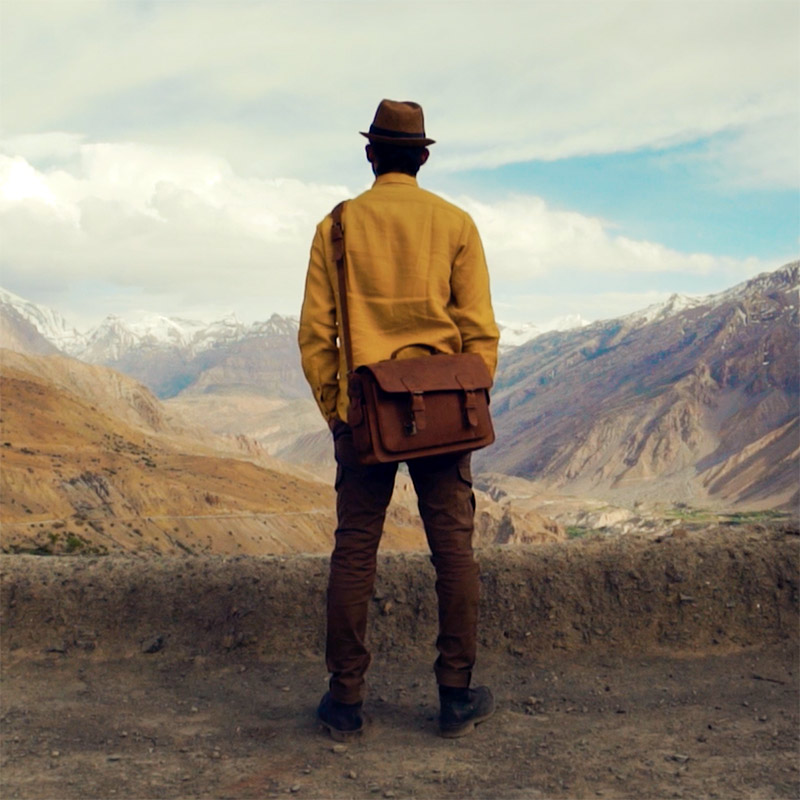 Man in the Hymalayas with brown leather bag and yellow shirt.