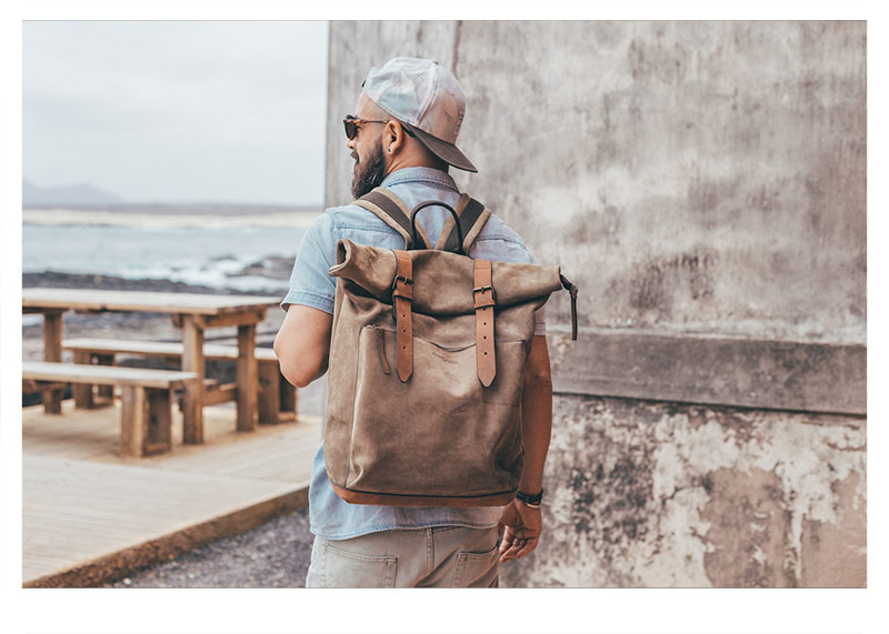 Man traveling with a leather backpack.