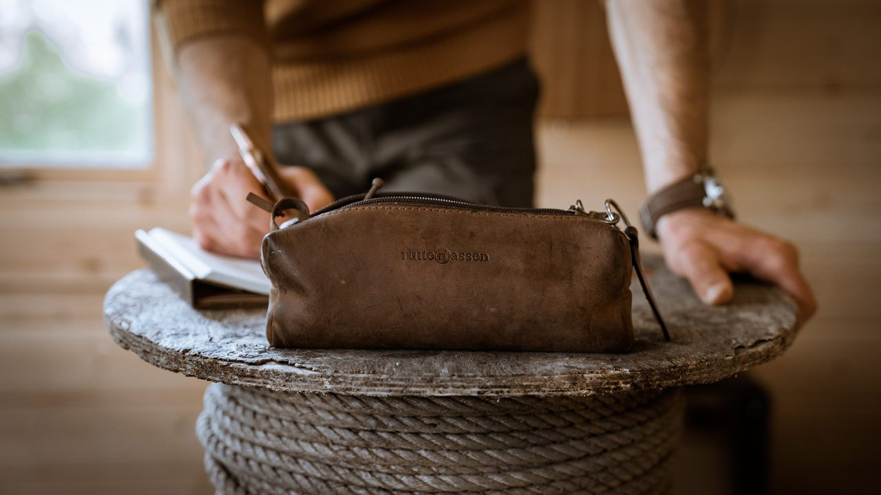 Man writing with a leather pencil bag at the foreground.