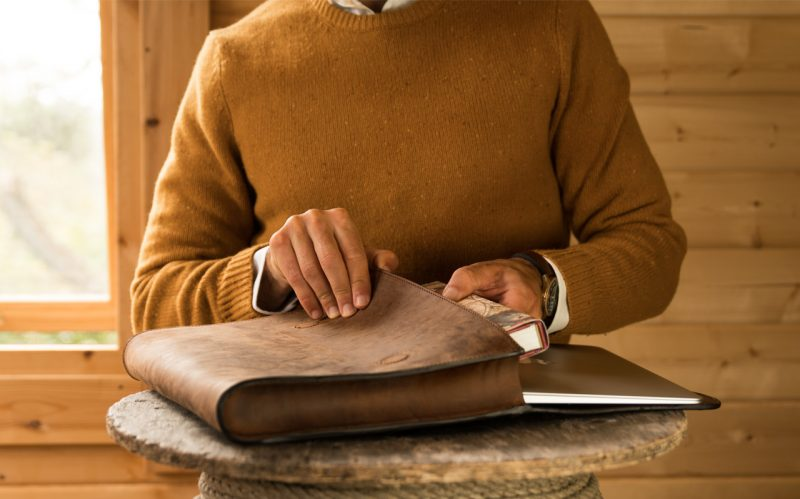 Man with brown leather document folder.