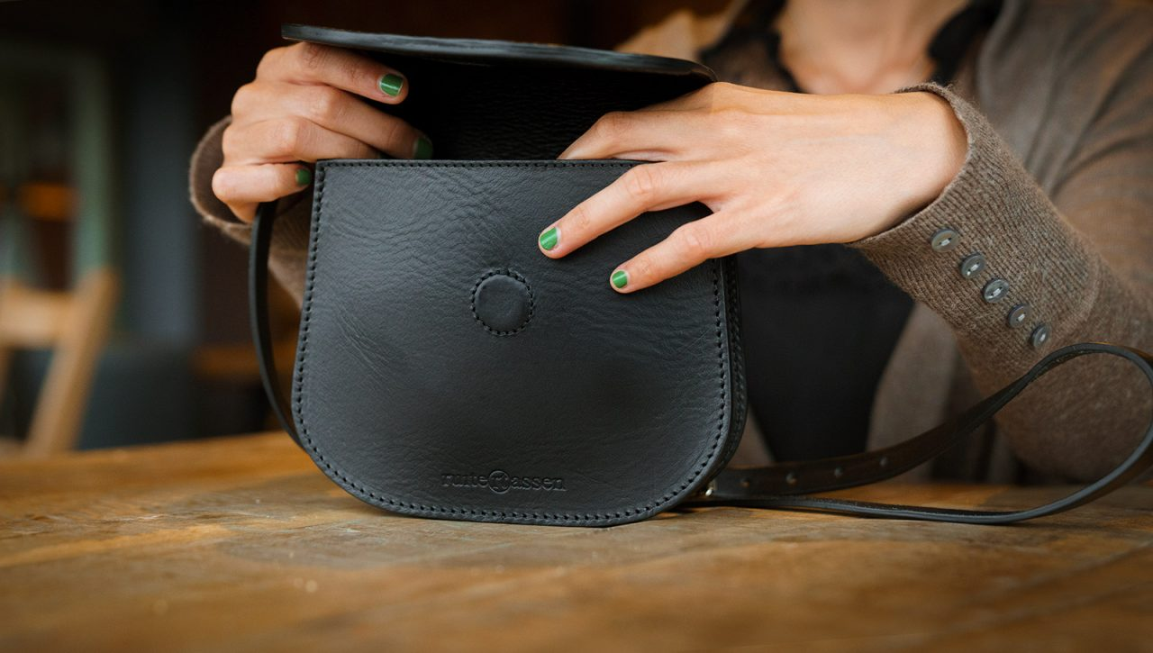 Women opening small black leather shoulder bag.