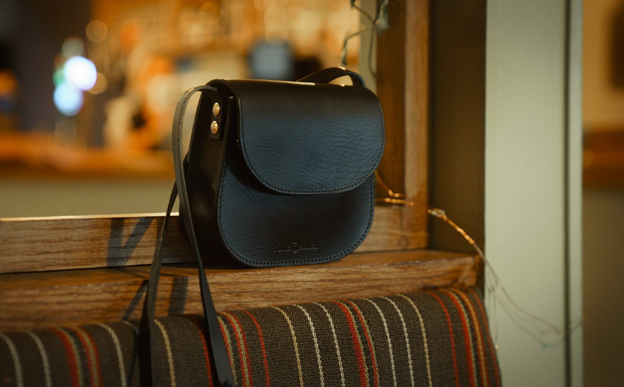 Small black leather shoulder bag in a cafe.