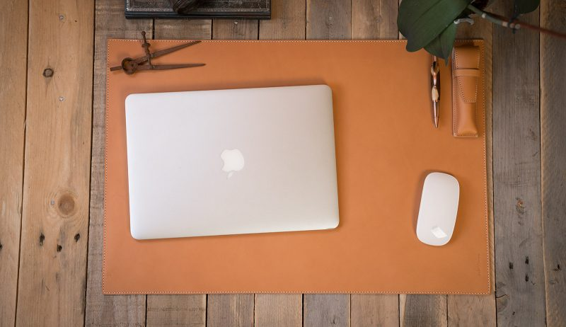 Leather desk mat with computer and mouse.