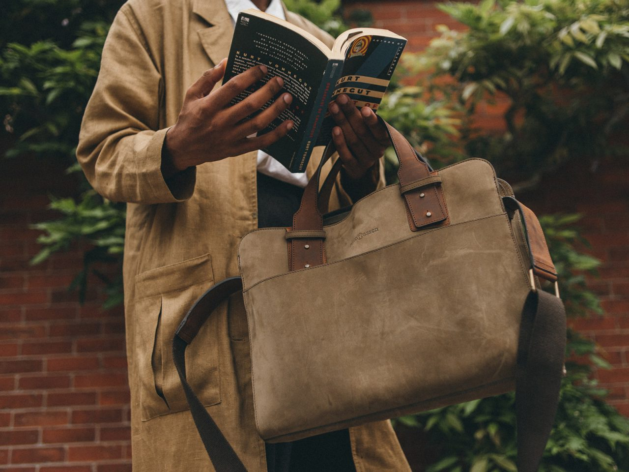 Man reading and holding a dark green leather briefcase.