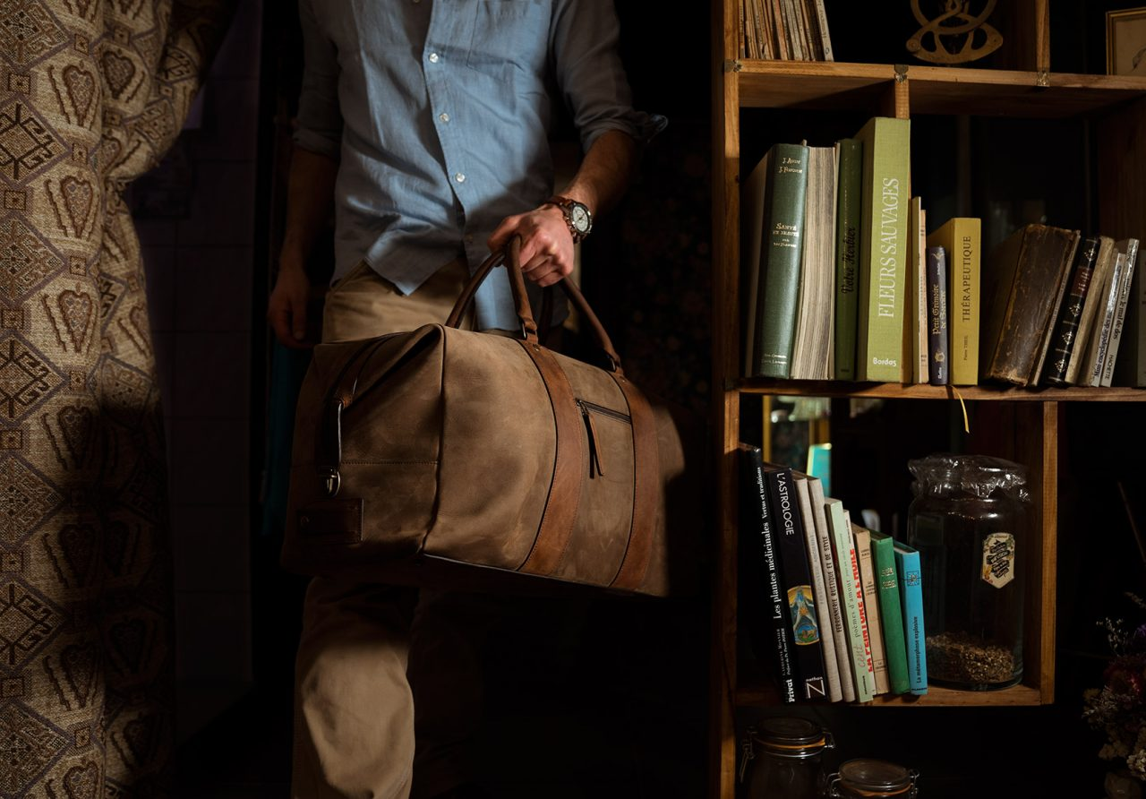 Man carrying leather duffle bag.