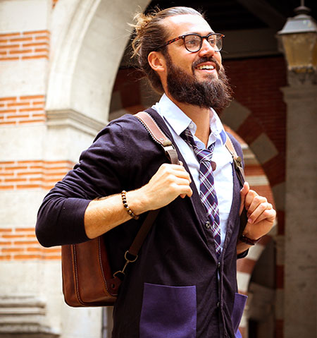 Man wearing a classic leather satchel like a backpack.